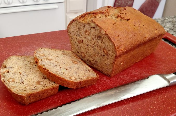 banana bread with knife on cutting board