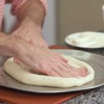 hand spreading pizza dough on pizza pan
