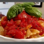 Tomato Sauce on farfalle pasta in white dish with basil