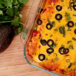 chicken enchiladas in a baking dish. Cilantro and Avocado.