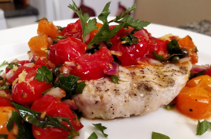 grilled swordfish with tomatoes and capers on a plate