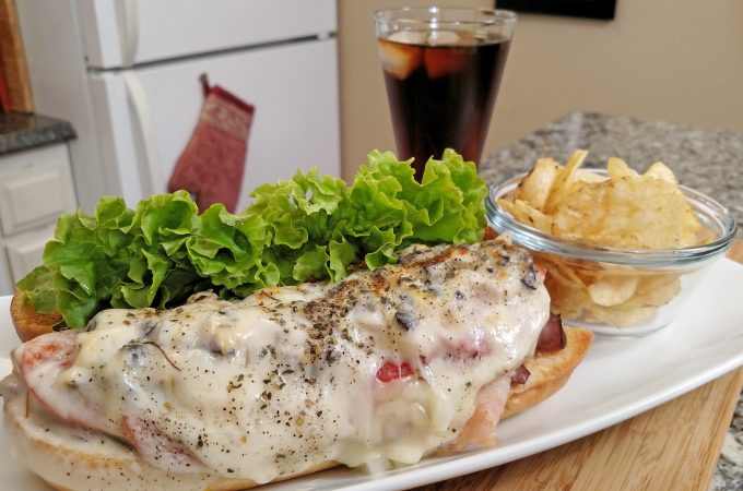 sandwich on a plate with soda and chips