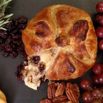 baked brie with grapes, crackers, rosemary on black table