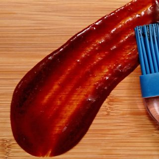 Homemade BBQ Sauce smeared on bamboo cutting board with brush
