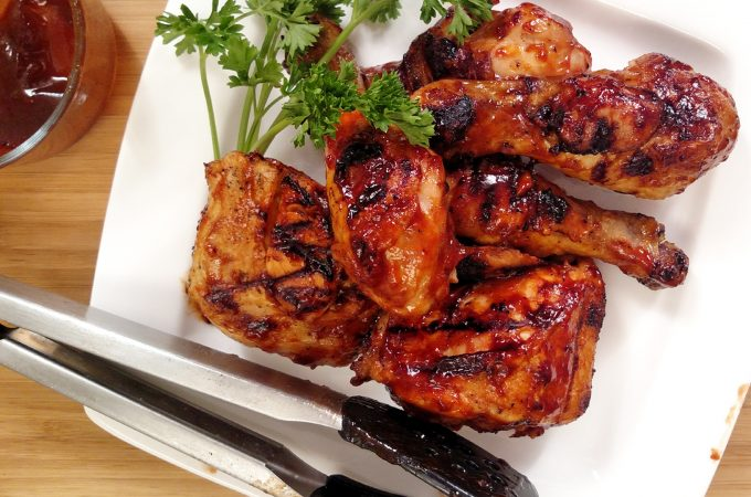 Indoor BBQ Chicken Grill on white plate with tongs, bbq sauce, parsley, bamboo cutting board