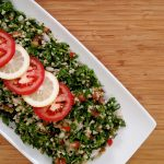Tabouli salad, sliced lemon, sliced tomato on white plate on bamboo cutting board