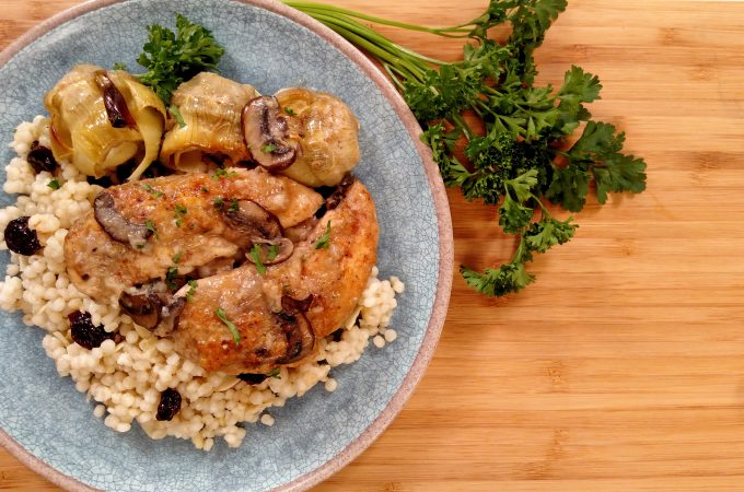 Chicken, Artichokes and mushrooms on a blue plate on bamboo cutting board with parsley