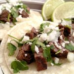 Street Tacos on corn tortilla with chopped onion, cilantro and lime wedges