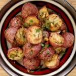 Roasted potatoes on a multicolored plate on bamboo cutting board