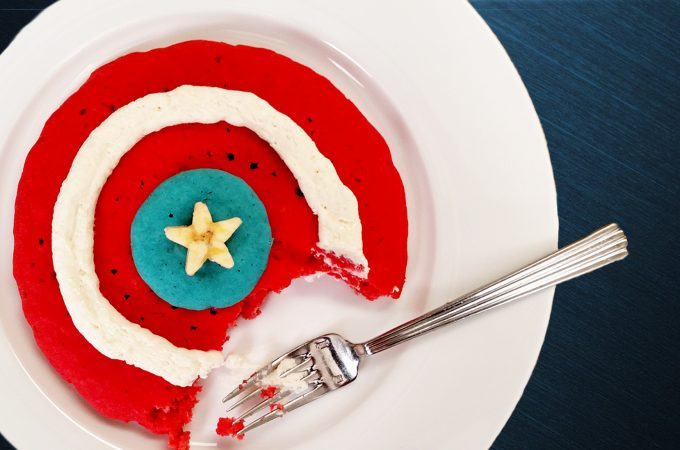 Captain America Shield Pancakes, red white blue pancakes with folk and banana star on white plate