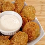 Fried Pickles ramekin of ranch dressing on white plate on bamboo cutting board