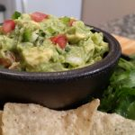 Guacamole in a black bowl with chips