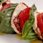 Caprese Salad, mozzarella, tomatoes, basil with a Balsamic Glaze and olive oil on white plate