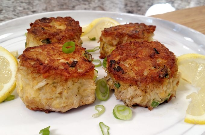 food network award winning crab cakes on a white plate with green onion garnish
