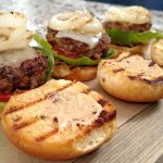 Hamburger Sliders on a wood cutting board, grilled onions, cheese