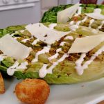 Grilled Caesar Salad and crouton and cheese on White plate in kitchen