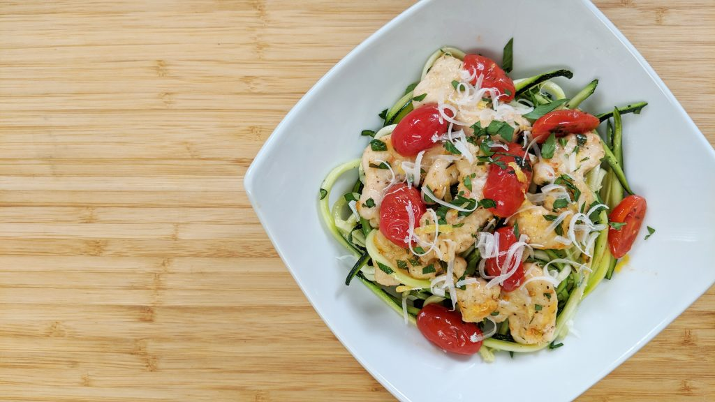 Zoodle Lemon Chicken with zoodles, tomatoes, lemon , chicken on white plate on bamboo cutting board
