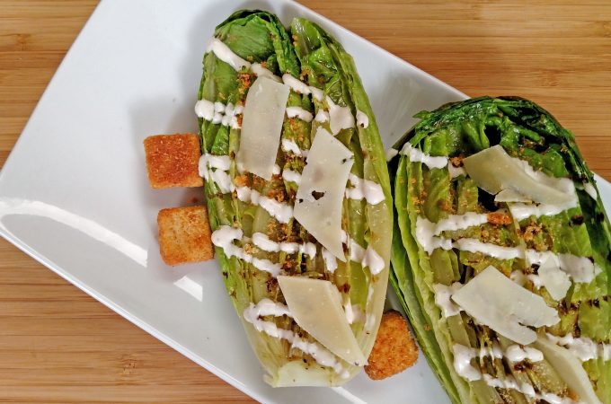 Grilled Caesar Salad drizzled with dressing, croutons, shaved parmesan cheese on white plate on bamboo cutting board