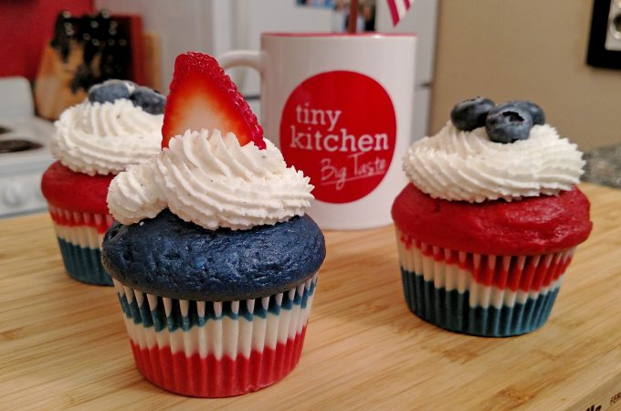 Red, White and Blue Velvet Cupcakes with Buttercream frosting, blueberries and strawberries with a Tiny Kitchen Big Taste coffee mug
