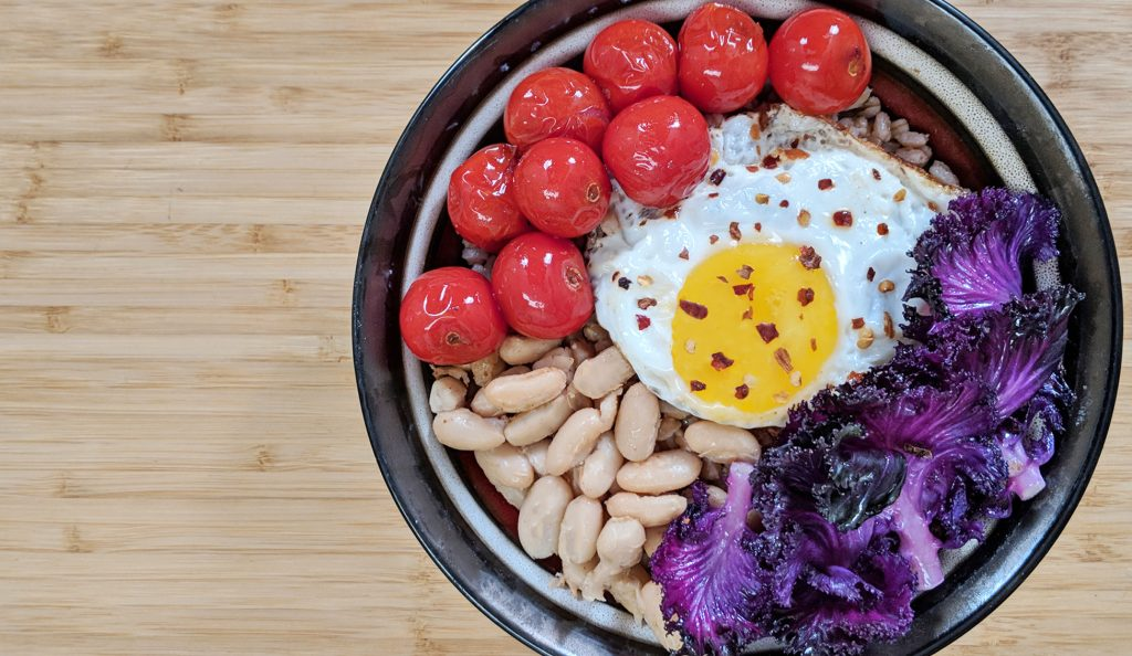 Farro Grain Bowl with Purple Kale, Cherry Tomatoes, Cannellini Bean and a Fried Egg with Red Pepper Flakes