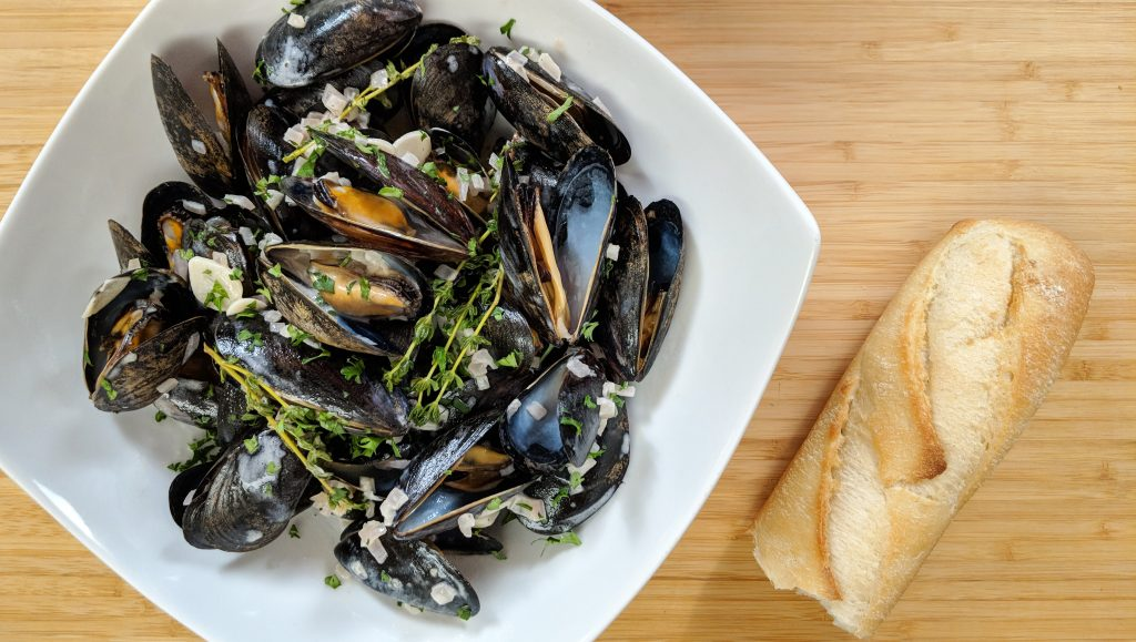 A bowl of black mussels with a crusty baguette. Garlic, shallots and thyme flavor the dish.