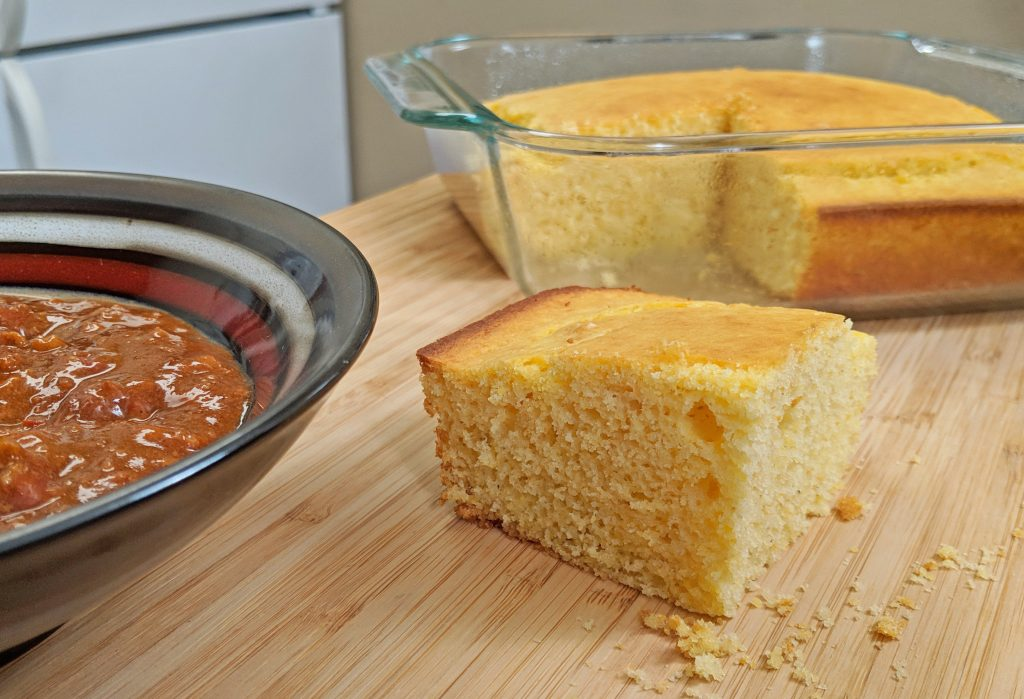 Piece of Cornbread with Pan of Cornbread with Bowl of Chili