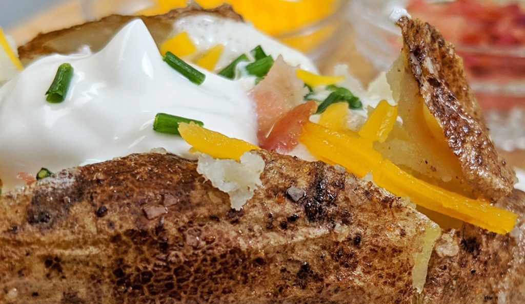 Close up of a baked potato with flaked salt chives, bacon, sour cream, butter and cheddar cheese