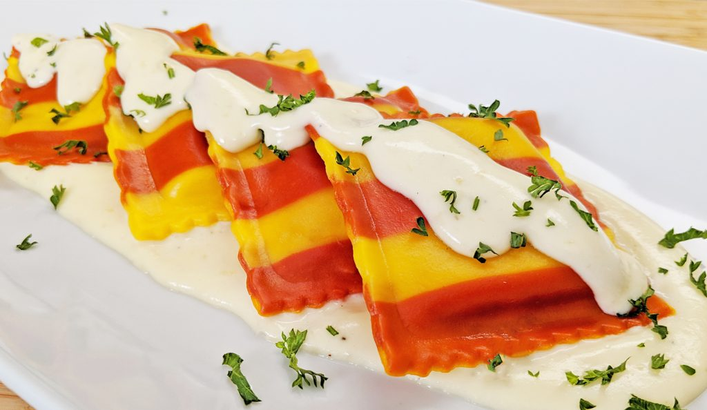 Red and Yellow Striped Lobster Ravioli with Cream Sauce plated on white plate with parsley