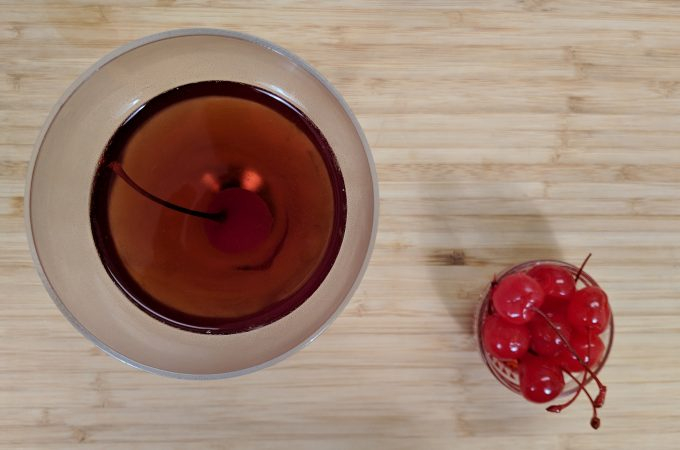 Ovehead view of manhattan cocktail in nick and nora glass with maraschino cherries on a bamboo cutting board