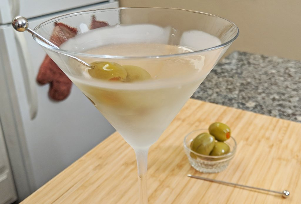 martini served in a frosted martini glass with olives on a bamboo cutting board