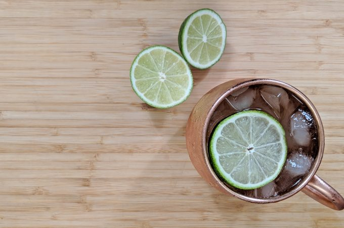 Overhead view of a Moscow Mule in a copper mug with a cut lime on a bamboo cutting board