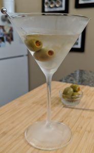 martini in a martini glas with olives on a wood cutting board