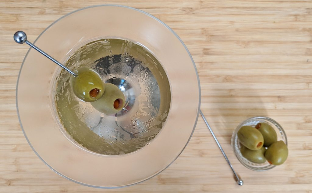 overhead view of a martini with olives on a bamboo cutting board