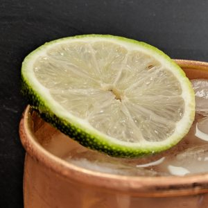 Closeup of Moscow Mule in Copper Mug with slice of lime and black background