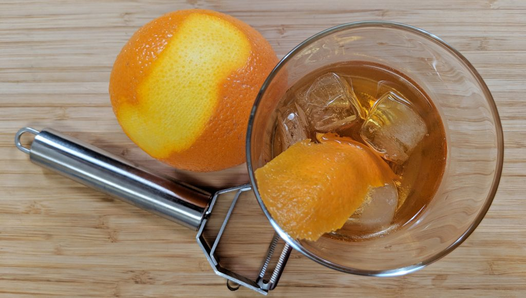 Overhead View of Old Fashioned Cocktail with Vegetable Peeler and Peel Orange and Orange Rind on a Bamboo Cutting Board