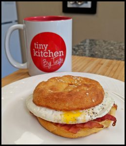 Keto Bagel Egg Sandwich with Bacon on a white plate with a Tiny Kitchen Big Taste Coffee Mug