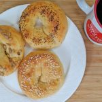 Overhead view of Keto Bagels with Sesame Seeds and Poppy Seeds and Sunflower Seeds on a white plate with a Tiny Kitchen Big Taste Coffee Mug