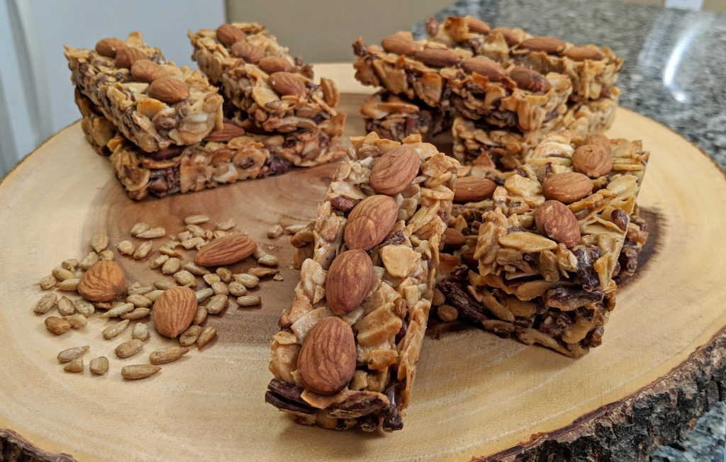 Tiny Kitchen Zip Bars (Keto Granola Bars) with Almonds, Coconut, Sunflower Seeds, Pecans stacked on a wooden board
