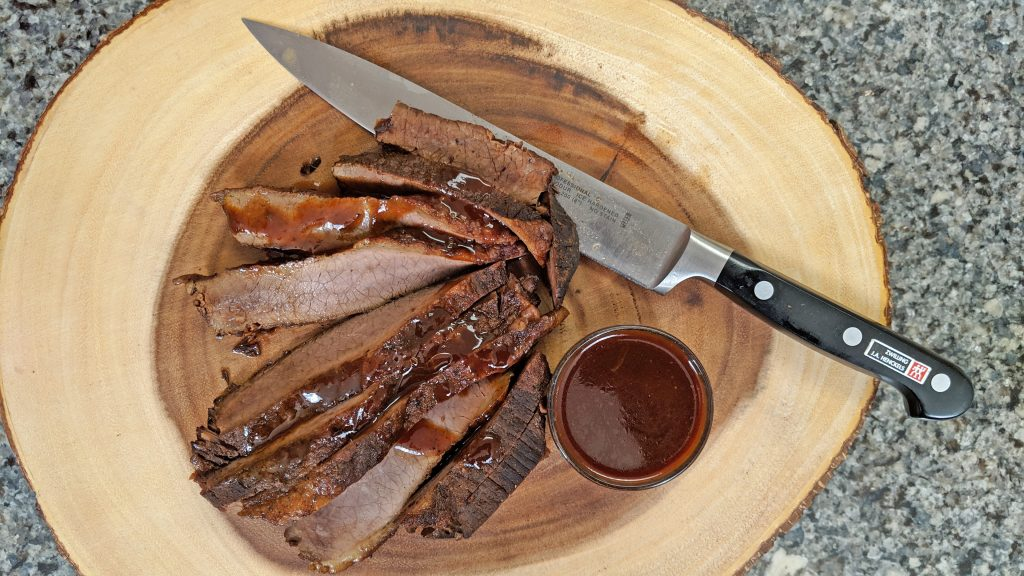 Sliced Brisket on cutting board with knife and bbq sauce