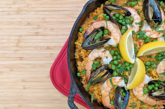 Paella with shrimp, mussels, saffron rice, peas and lemon in a black pan