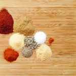 piles of spices on bamboo cutting board
